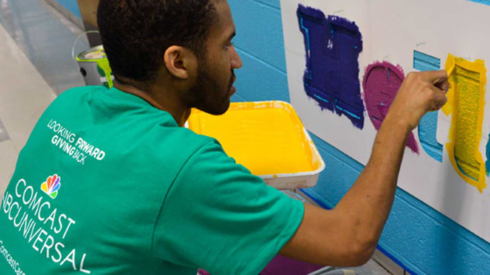 Comcast Cares Day volunteer painting mural