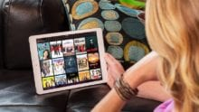 A person uses their tablet to navigate the Xfinity Stream app