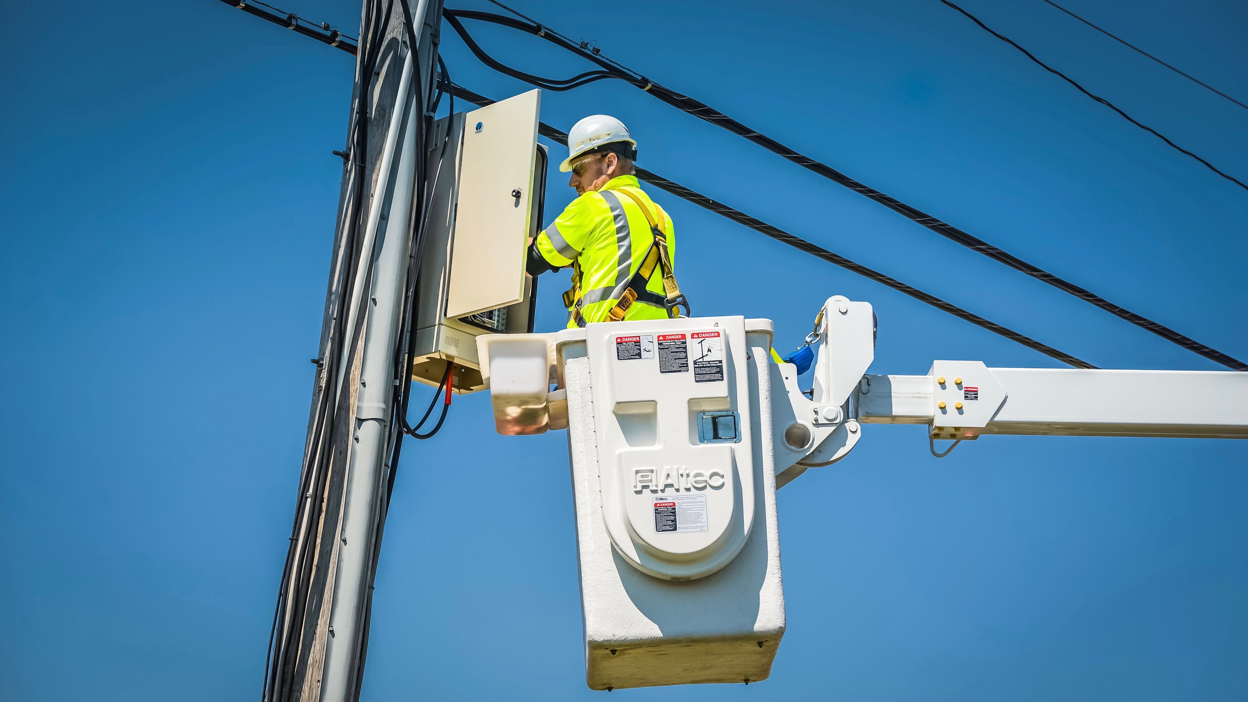 An Xfinity technician repairs equipment on a telephone pole.