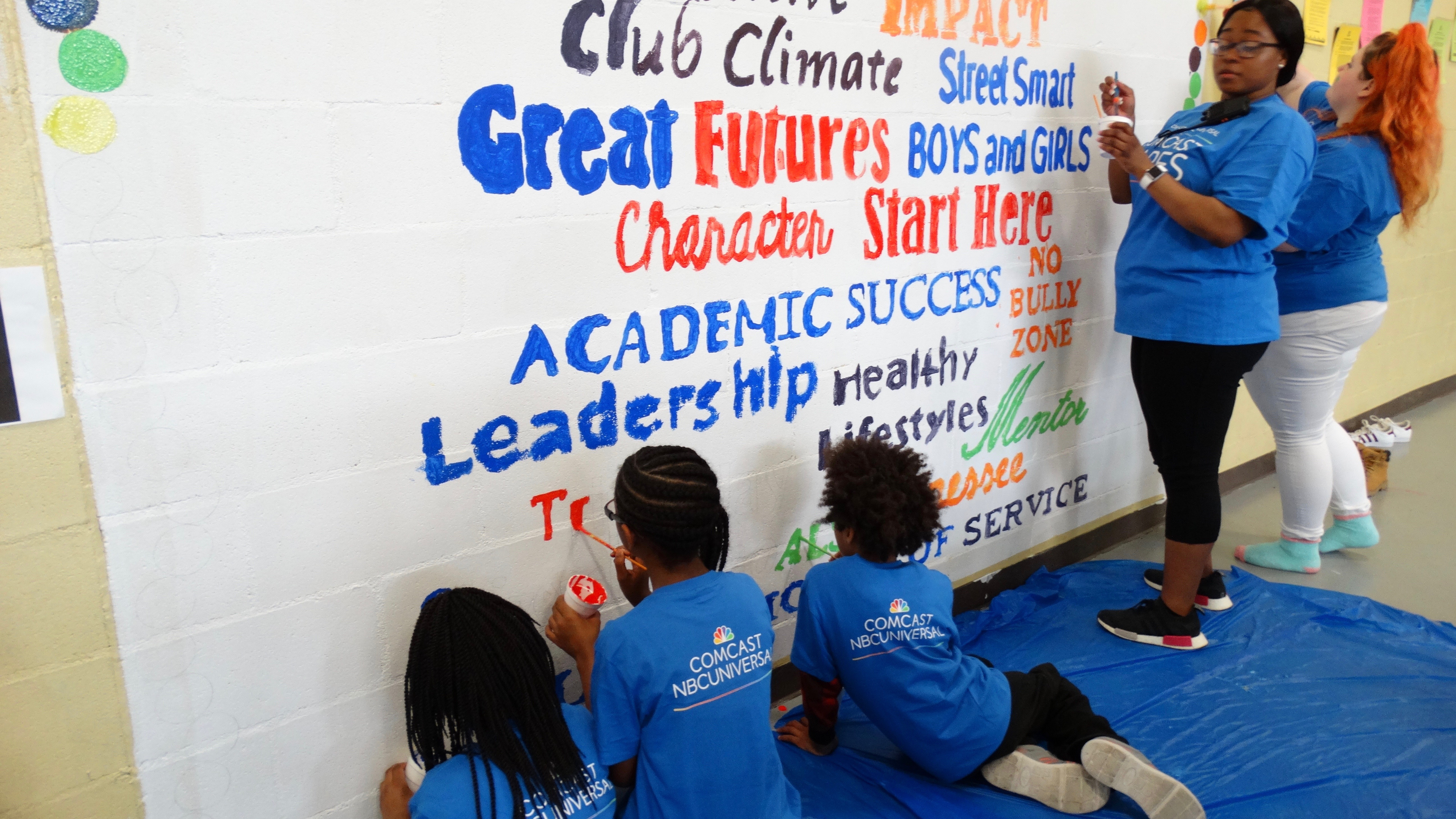 Young Comcast Cares Day volunteers paint a mural.