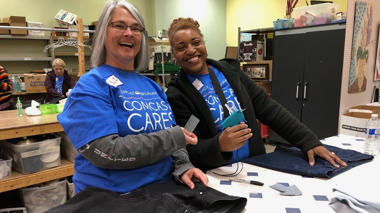 Two Comcast Cares Day volunteers sort clothing donations.