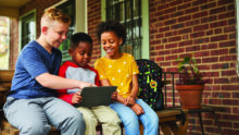 Three children use a tablet as they sit on a porch.